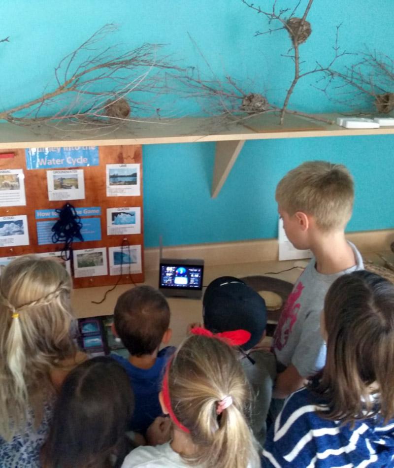 Children observing AcuRite Atlas display