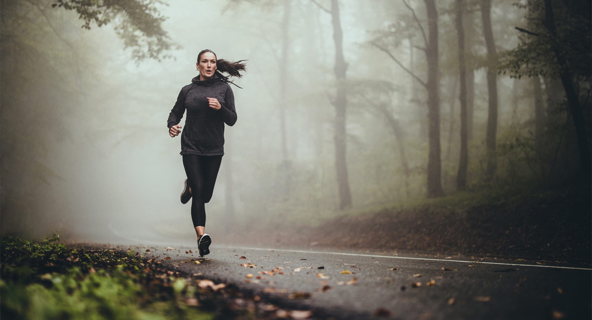 Woman running on wet road
