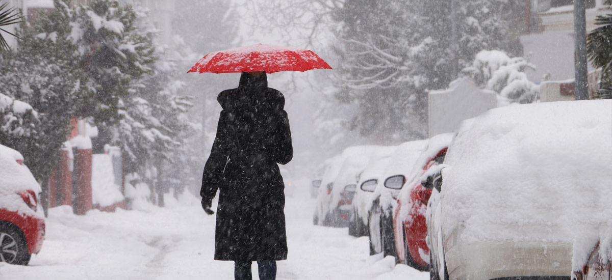 Woman walking through the snow with an umbrella