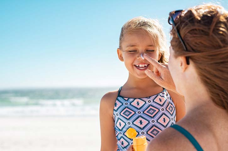 Mom Putting Sunscreen on Smiling Child