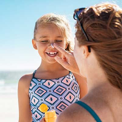 Mom Putting Sunscreen on Child's Nose